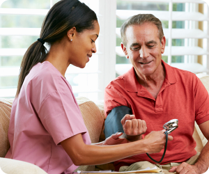 caregiver checking elderly man's blood pressure
