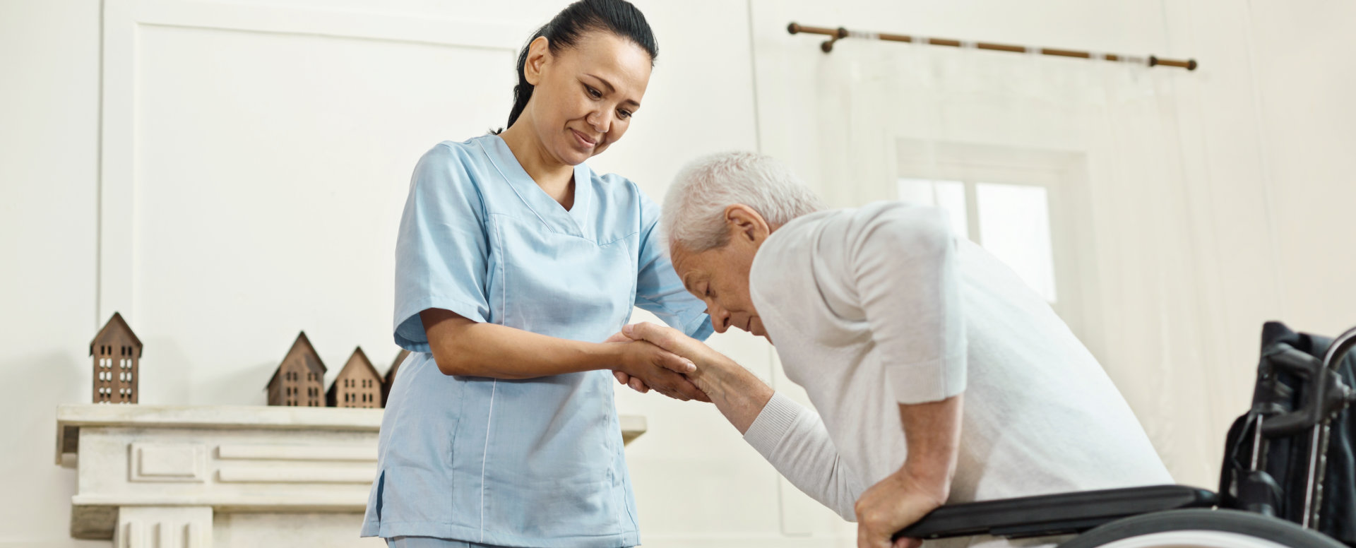 caregiver assisting her elderly patient to stand