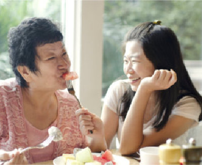 mother and daughter happily eating together